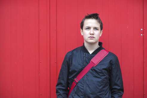 Portrait of serious looking teenage boy in front of red door - MVC000150