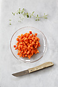 Glass bowl of diced carrots and a kitchen knife on white ground - EVGF001034