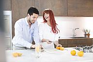 Couple in kitchen making fresh orange juice - ZEF002653