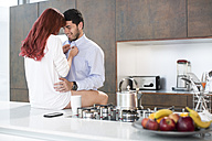 Couple in kitchen sharing an intimate moment - ZEF002656