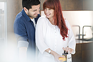 Couple in kitchen grating cheese - ZEF002661