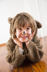 Portrait of smiling little girl masquerade as a bear lying on wooden floor - LVF002453