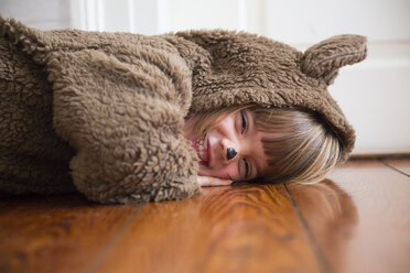 Portrait of laughing little girl masquerade as a bear lying on wooden floor - LVF002456