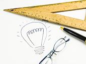 Drawn lightbulb, set square, reading glasses and ballpen on white paper - AMF003444
