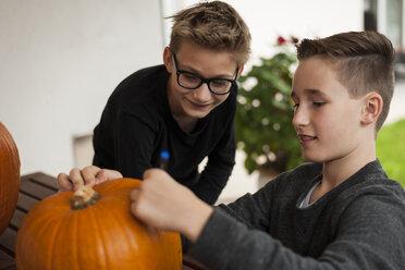Two boys preparing a pumpkin for Halloween lantern - PAF001098