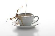 Milk splashing in a cup of coffee in front of white background - YFF000280