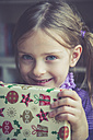 Portrait of smiling little girl holding Christmas present - SARF001160