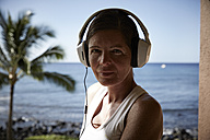 USA, Hawaii, portrait of woman with headphones in front of the sea - STKF001093