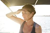 Spain, Balearic Islands, Mallorca, woman on a ship shielding her eyes - STKF001090