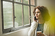 Young businesswoman on cell phone looking out of window - UUF002857