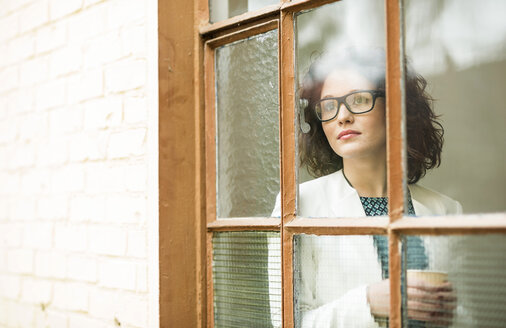 Young businesswoman looking out of window - UUF002870