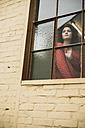 Young woman looking out of window - UUF002880