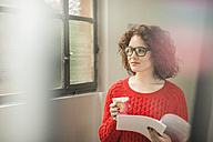 Young woman with document and coffee to go at the window - UUF002888
