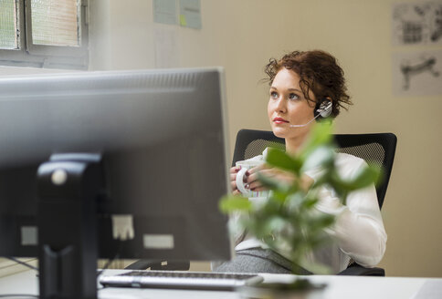 Young woman in office wearing headset - UUF002917