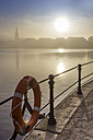 Germany, Hamburg, silhouette of town hall looming through the dense fog over the Alster lake - NK000216
