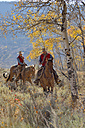 USA, Wyoming, Big Horn Mountains, riding cowgirl and cowboy in autumn - RUEF001300