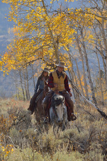 USA, Wyoming, Big Horn Mountains, riding cowgirl and cowboy in autumn - RUEF001331
