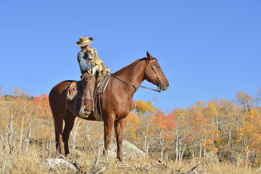 USA, Wyoming, Big Horn Mountains,  cowgirl sitting on horse with her dog - RUEF001321