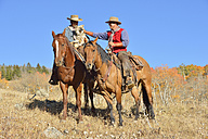 USA, Wyoming, Big Horn Mountains, riding cowgirl and cowboy in autumn - RUEF001322