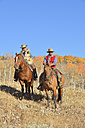 USA, Wyoming, Big Horn Mountains, cowboy and cowgirl on her horses in autumn - RUEF001323