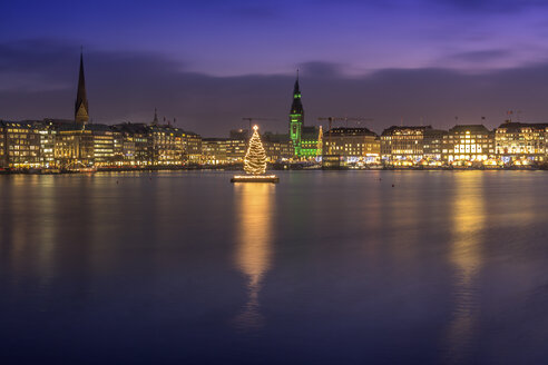 Germany, Hamburg, Downtown skyline with illuminated Christmas tree on Alster river - NKF000210