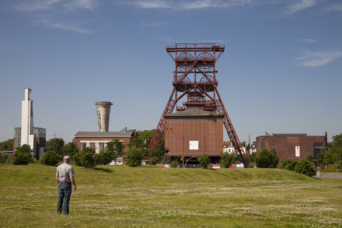 Germany, Ruhr area, Gelsenkirchen, man on meadow at disused coal mine Consolidation - WI001183