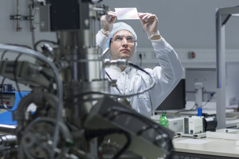 Technician in cleanroom examining sample - SGF001230