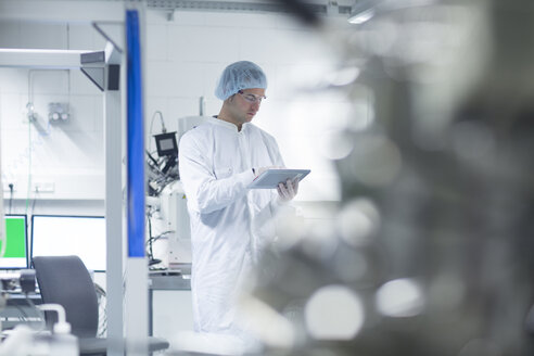 Technician in cleanroom holding digital tablet - SGF001233