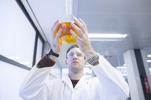 Chemist working in lab holding round bottom flask - SGF001245