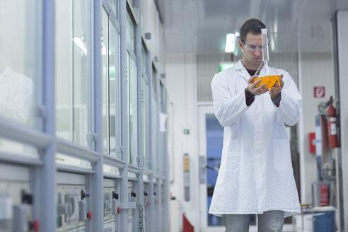 Chemist working in lab holding round bottom flask - SGF001247