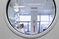 Scientist working in laboratory behind safety door - SGF001263