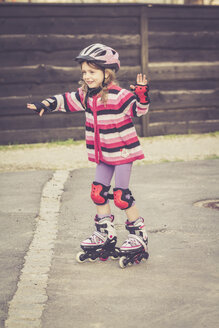 Little girl balancing on rollerblades - SARF001173