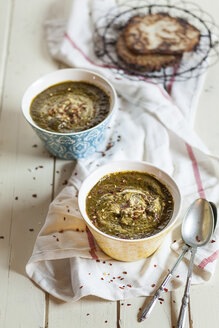 Bowls of Saag spiced with chili flakes on cloth - SBDF001537