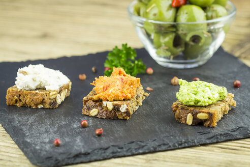 Slices of wholemeal bread with different sheep cheese spread on slate - JUNF000105