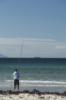 Spain, Andalusia, Tarifa, man fishing at seashore - KBF000258