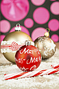 Three Christmas baubles and sugar cane on artifical snow in front of pink circles - JUNF000125