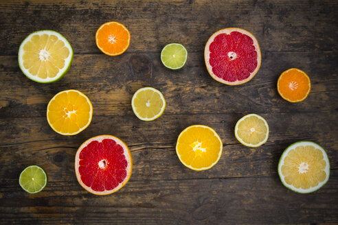 Slices of different citrus fruits on dark wood - LVF002476