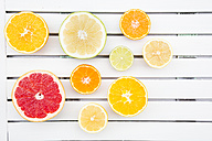 Slices of different citrus fruits on white wood - LVF002487