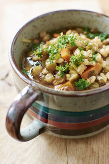 Cup of lentil barley stew with brown lentils, barley, onions, carrots garnished with  parsley - HAWF000538