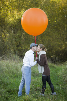 Couple with balloon on meadow kissing - JTLF000015
