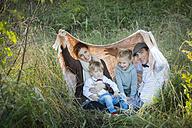 Happy family under blanket on meadow - JTLF000013