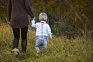 Mother with son walking on meadow - JTLF000010
