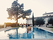 Spain, Majorca, young man jumping into swimmingpool - MS004400