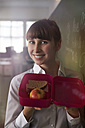 Smiling woman holding lunch box - STKF001134