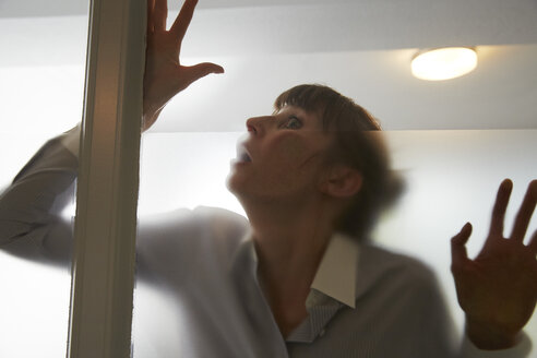 Frightened woman behind glass pane - STKF001137