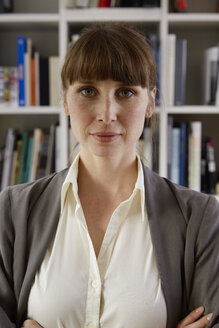 Portrait of woman in front of book shelf - STKF001140