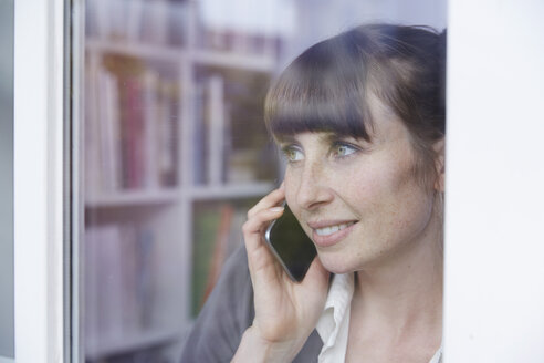 Woman behind glass pane on cell phone - STKF001143
