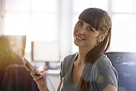 Smiling woman holding cell phone - STKF001184