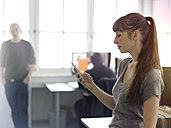 Woman in office looking at cell phone - STKF001185
