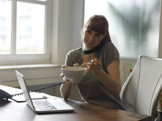 Smiling woman with laptop at desk on the phone eating from bowl - STKF001188